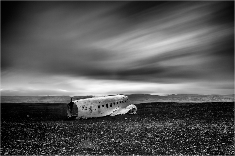 ----------------------------------------------------------------------------------------  In 1973, the US Navy airplane - a Douglas Super DC-3 - crash landed on Sólheimasandur beach in Iceland after what was later found to be a pilot's error. The crew all survived the impact, but the plane was abandoned rather than recovered - and lies there still in the middle of the black desert that surrounds it.  While this spot has become a lot more popular and accessible in the last few years, it was still on our list to visit and the experience of seeing the remains of the plane abandoned in the middle of nowhere was fascinating. Probably even just five years ago not many people would have known where to find it and how to get to it.  You can see the wreck in my photo and the desolate landscape around it. I went for a long exposure as the clouds were moving very fast and this gave the scene a bit of a surreal quality. I like the way the movement above contrasts with the stillness of the foreground.  Thank you all for viewing and commenting and I hope you continue to enjoy my perspective of Iceland :-)