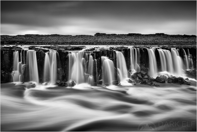 ----------------------------------------------------------------------------------------  This is a view from the east bank of Jökulsá á Fjöllum river in northern Iceland, near the Selfoss waterfall. On a different day we returned to the waterfall and due to the main fall being covered almost entirely by water spray, I decided to concentrate on some of the run off streams on the western side of the river.  Luckily, the wind was blowing away from the camera and kept the water spray away from my filters. I was fascinated by the various flows in the scene before my eyes. The smooth texture of the clouds, vertical streams running down the cliffs and horizontal flow of the river working in unison together.  I was very pleased with this photo. The conversion to monochrome worked very well and it is one of my favourite (if not the favourite) photos from the entire trip.