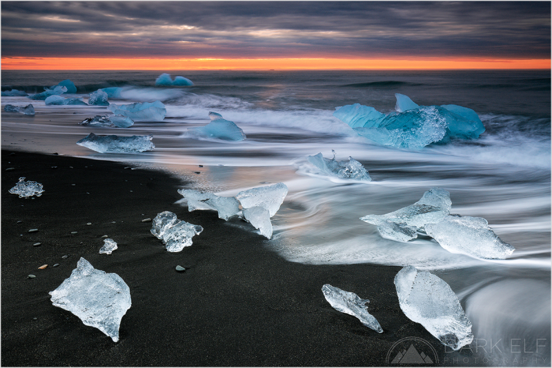 ----------------------------------------------------------------------------------------  Breiðamerkursandur  - that is the Icelandic name for the black sand beach near Jokulsarlon Glacier Lagoon where many of the icebergs return to shore after being pushed out to sea by the receding waters of outgoing tide.  It was a bit tricky shooting the icebergs because of the incoming waves and the imminent danger of one of the icy bits crashing into my legs or my tripod. I have purchased a pair of wellington boots in Reykjavik and they came in very handy that morning. In addition, the icebergs were pushed around all the time and timing the shutter button was crucial to capturing as many of the as still as possible.  It was a glorious morning, may be without too much sunrise colour, but the ice show on the black beach more than made up for that. Despite seeing numerous photos in the past, I could never quite envision what it was going to be like in real life. Spectacular - that is what it was!