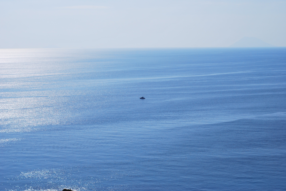 A boat alone in the middle of the blue sea