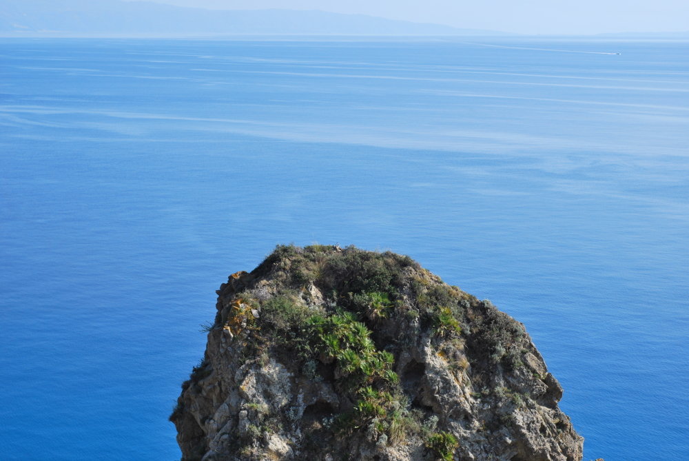 A view of a rock in the middle of the sea in Italy