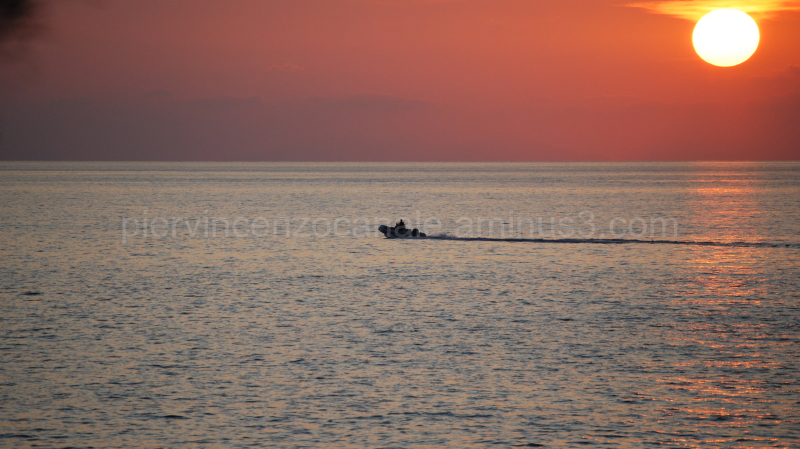 Sunset over the Mediterranean sea with a boat.