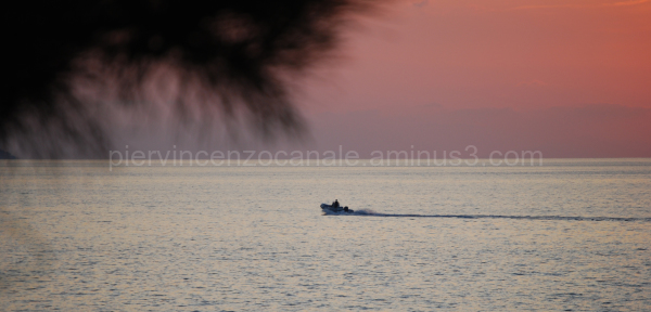 A boat in the Mediterranean sea at sunset, Italy.