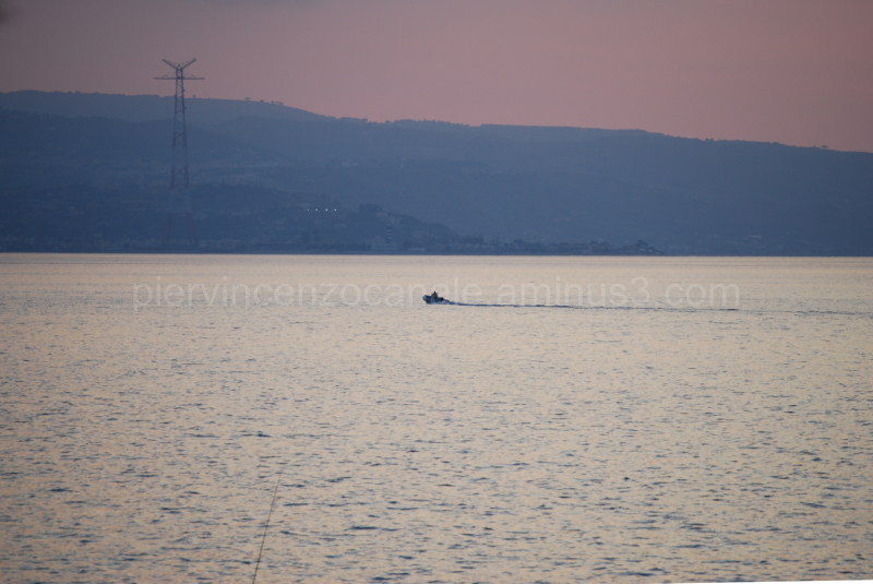 A boat, a fisherman rod and a beautiful sunset.