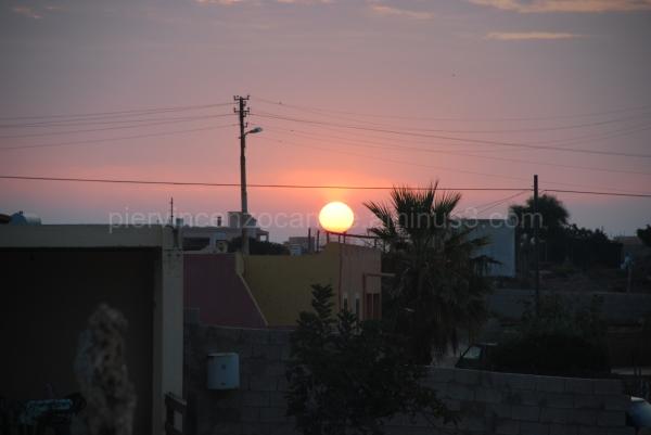 Una vista del tramonto tra le case di Lampedusa.