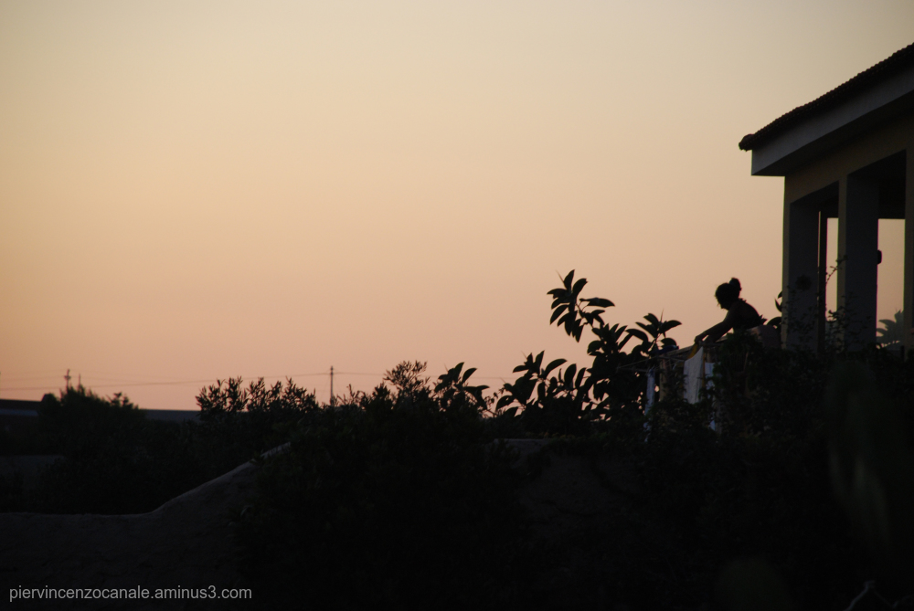 Sunset view in Lampedusa with a woman working.