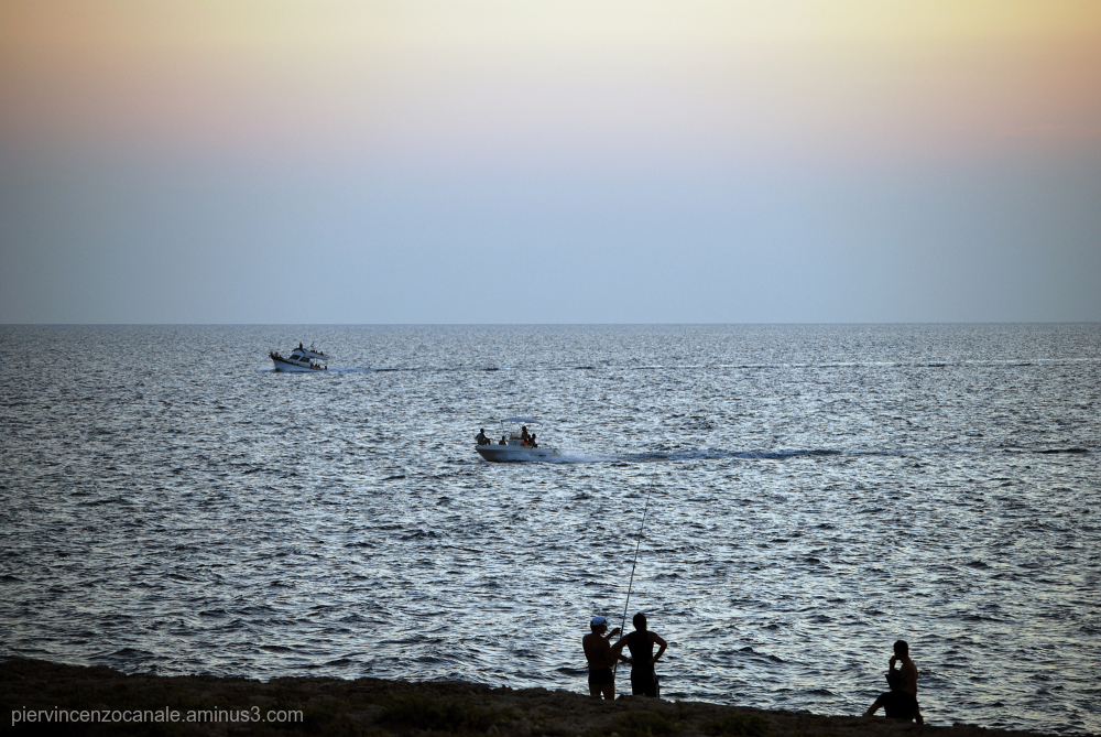 People fishing and boats passing by in Lampedusa