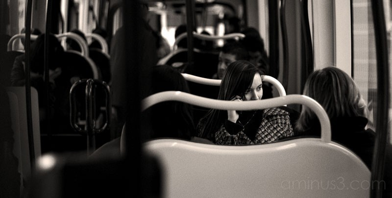 Young woman on tramway talking on a cell phone.