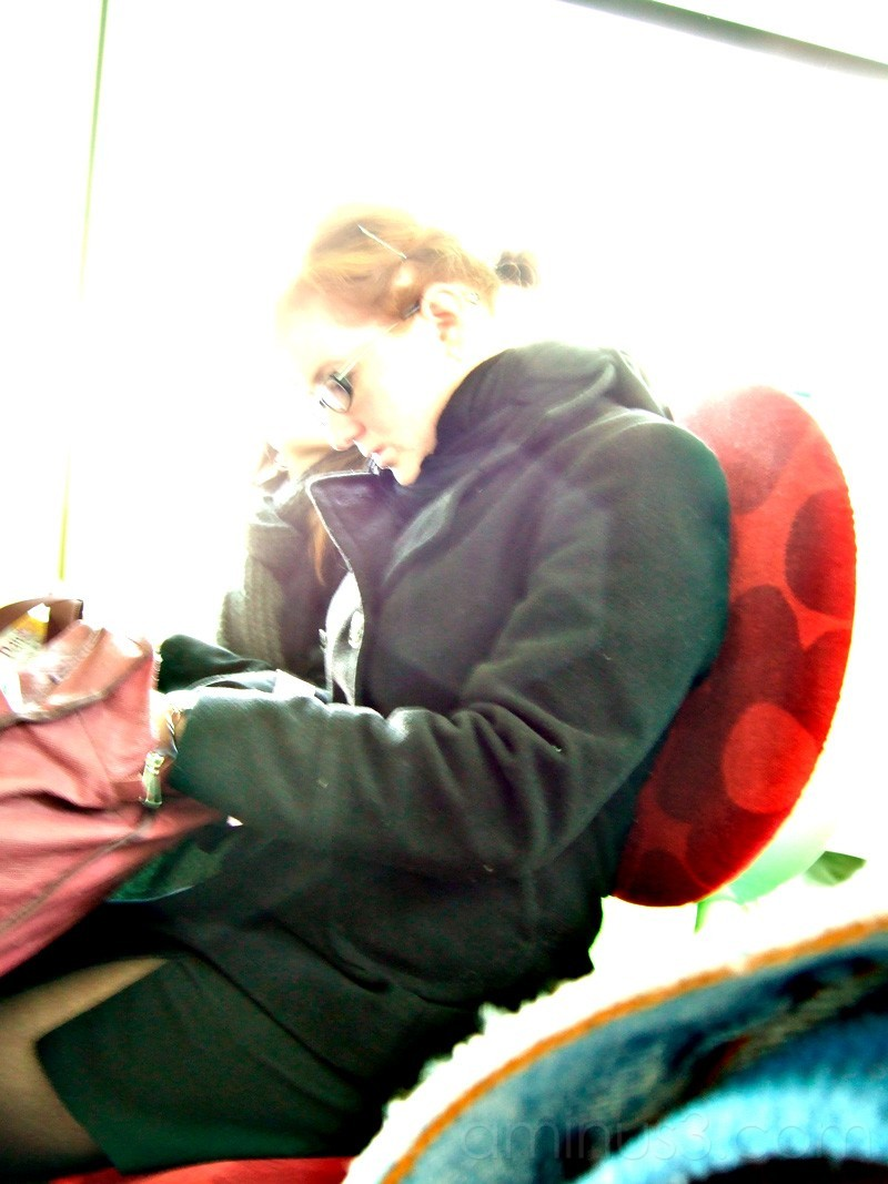 Young woman on tramway searching her bag.