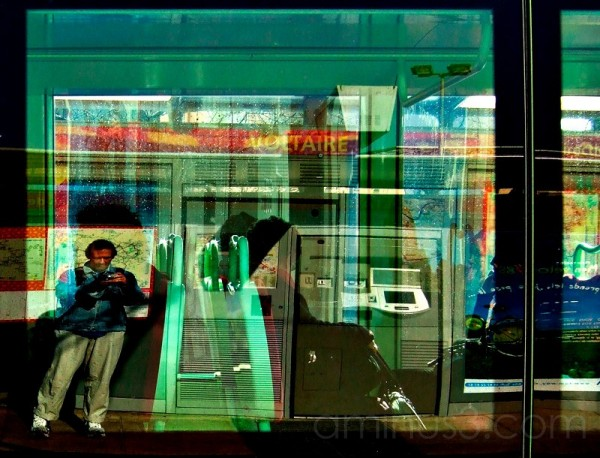 Photographer reflection in passing tramway.