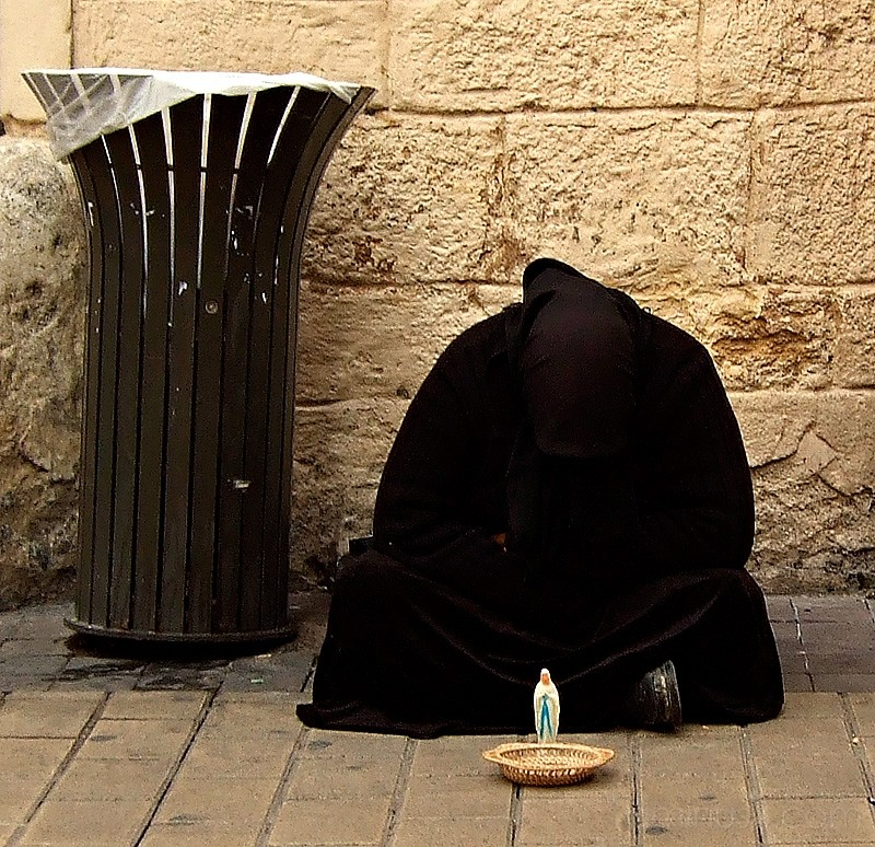 Woman beggar in black in France.