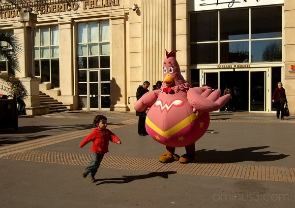 Child playing with person in chicken costume.