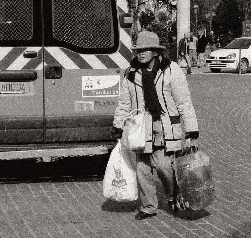 Older woman with shopping bags and cool hat.