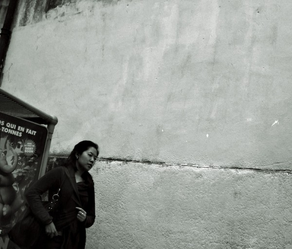 Chinese woman walking near a wall in France.