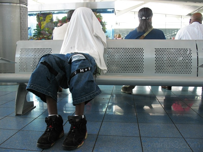boy waiting for ferry with shirt over head