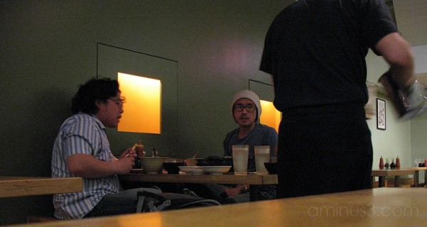 Two men eating at a restaurant in Manhattan.