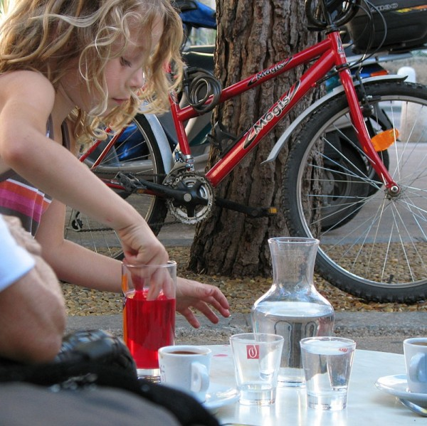 Young girl mixing her drink with her fingers.