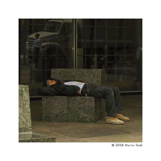 Boy sleeping on marble bench in Manhattan.