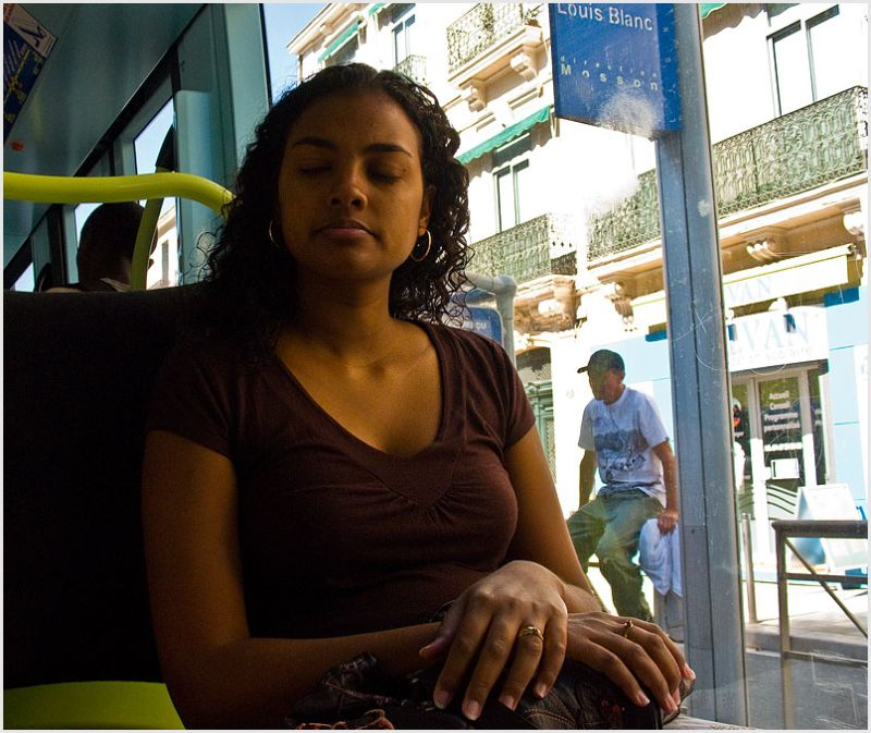 Young woman with eyes closed on tramway in France.