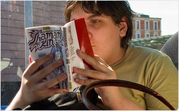 Boy reading Shaman King on the tramway.