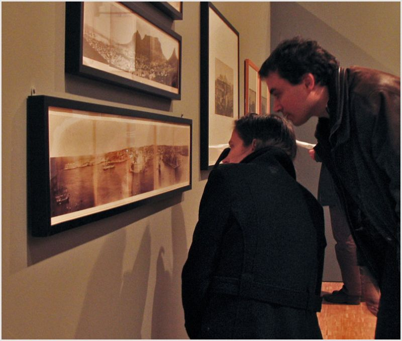 Man, woman, closely inspecting a photo.