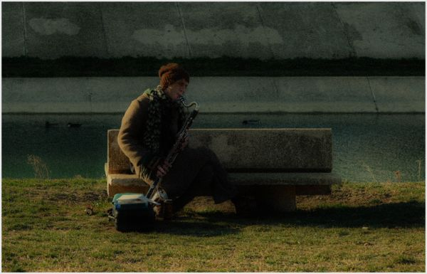 Man playing sax by the river.