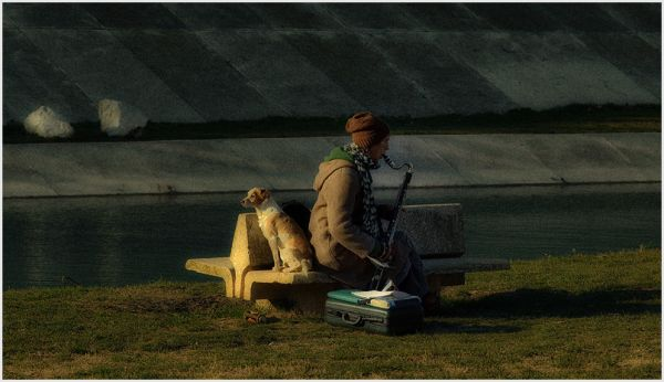 A man and his dog playing sax near a river.
