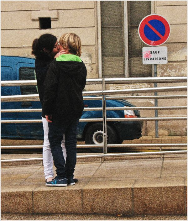 Two young kids kissing on the street in France.