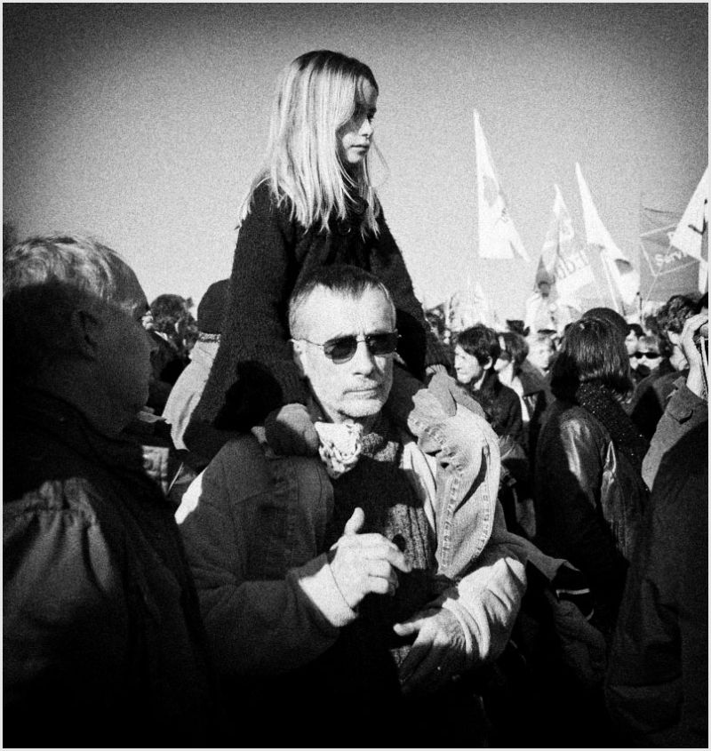 Girl on father's shoulders at a protest march.