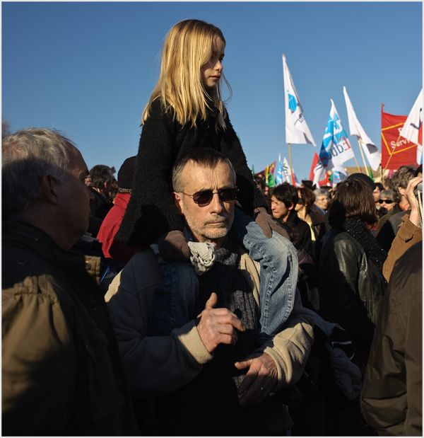 Young girl on her dads shoulders in a march.