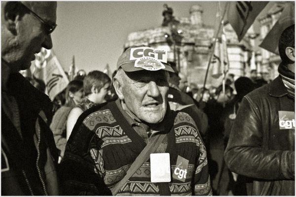 Older man walking in a protest against Sarkozy.