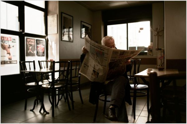 Man reading paper in a cafe in the south of france