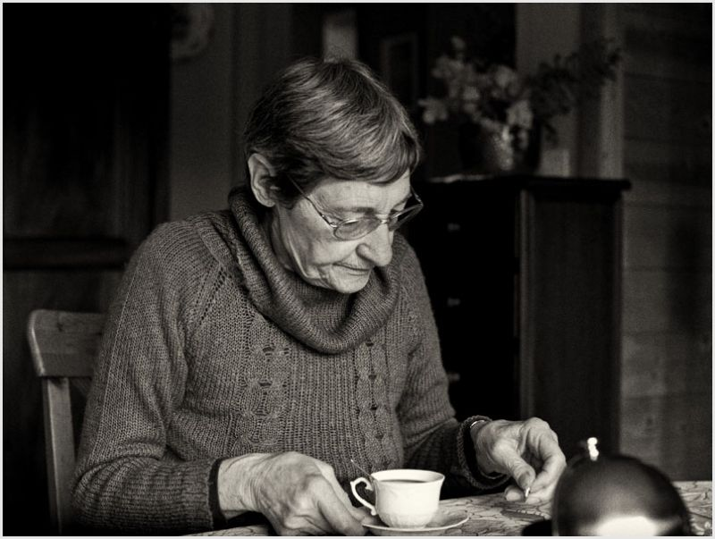 An older woman with tea looking at something.