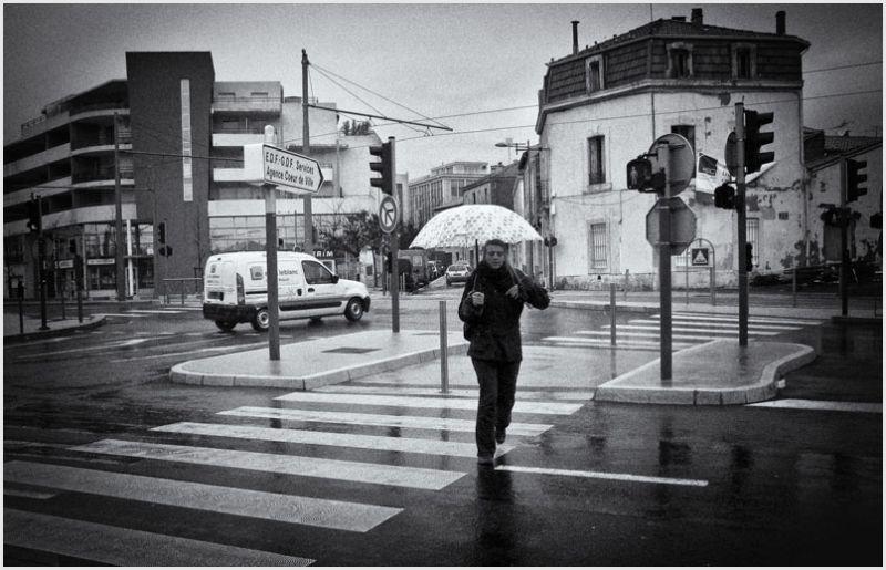 A woman walking in the rain umbrella in hand.