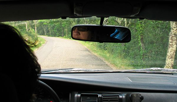 Photo in car of road and driver in mirror.