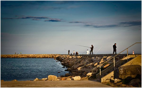 People fishing on a jetty in the south of france.