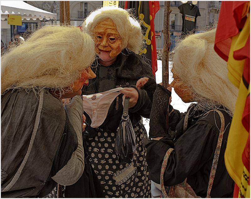 Three women in costumes looking at panties.