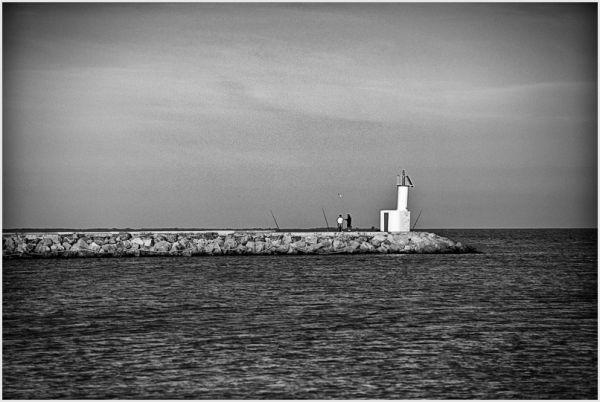 B&W sea image with fishermen on jetty.