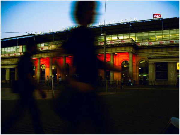 Two men walking in front of railway station.