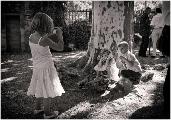 Girl taking photo of two children.