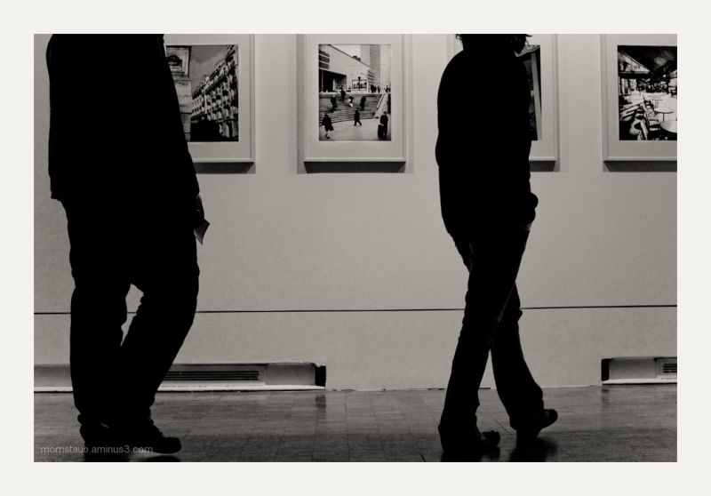 Couple looking at photos in a gallery in France.