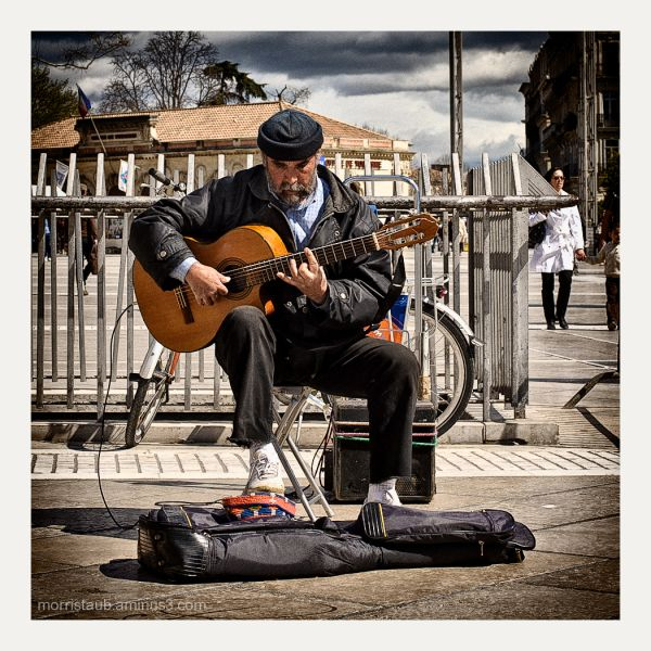 Man playing guitar in a french square.