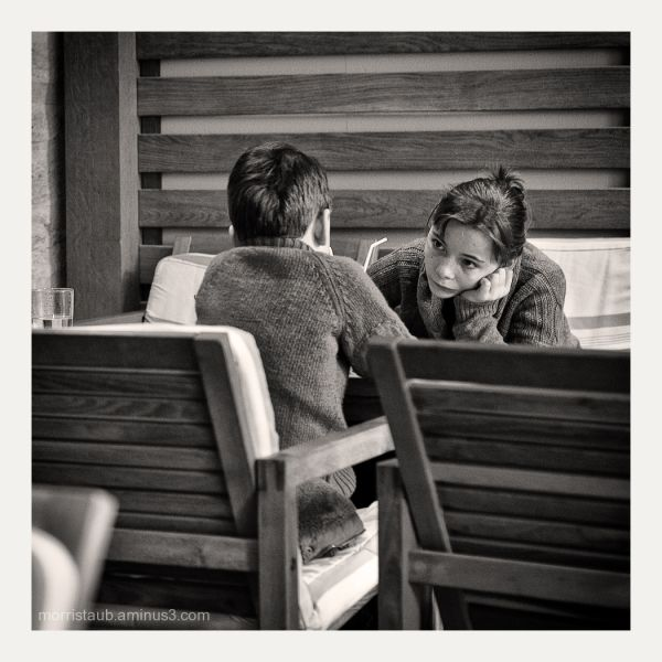 Brother and sister talking in a cafe.