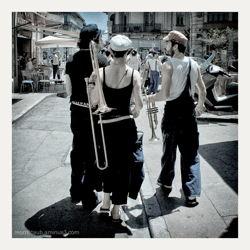Musicians holding instruments walking in street.