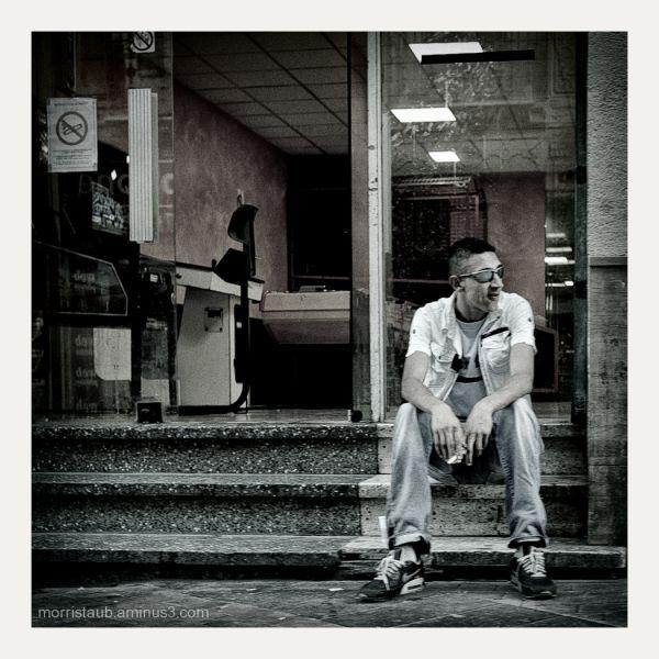 Young man smoking outside a games arcade.