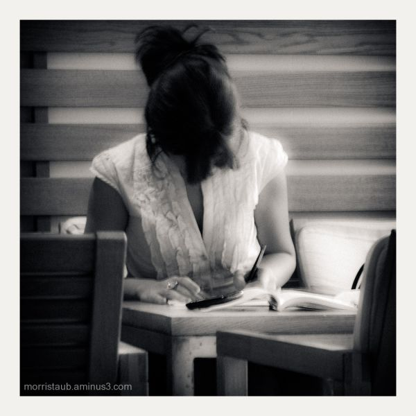 Woman writing in a cafe.