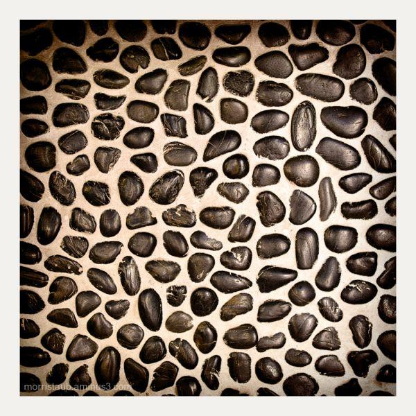 Detail of black stones in concrete.