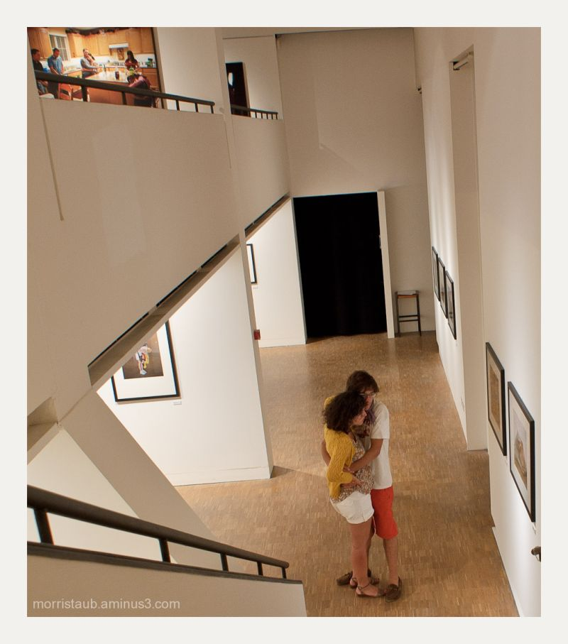 Couples hugging in gallery and in photo.