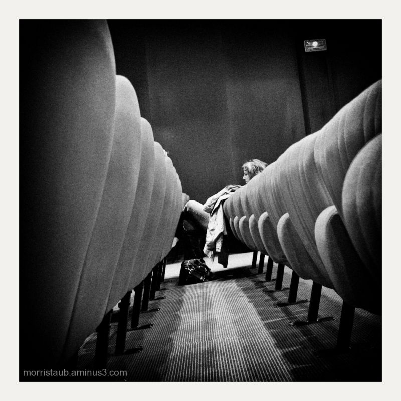 A woman sitting at end of row of seats in theater.