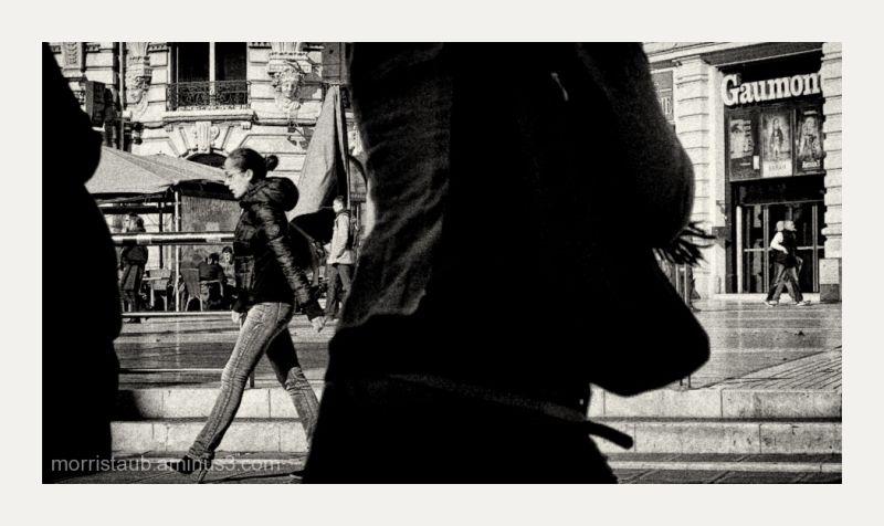 Woman walking between two dark figures.